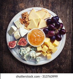 Cheese plate served with grapes, jam, figs and nuts on a wooden background