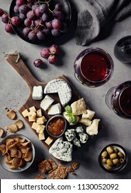 Cheese plate served with red wine, olives, grapes, jam and bread snacks on gray marble background. Top view.