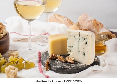 Cheese plate served with white wine, grape and nuts