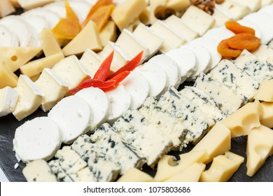 Cheese plate with variety of cheeses sliced on a stone