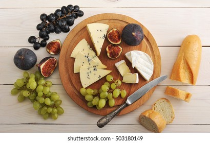 cheese plate - various types of cheeses and figs and grapes on a white wooden background - top view