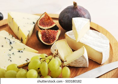 cheese plate - various types of cheeses and figs and grapes on a white wooden background - macro