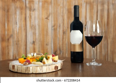 Cheese plate with various types of cheeses. A bottle of wine, glass of red wine. Wine drink and light snack. Delicious dinner, arrange a party, Food and drinks concept. Copy space, wooden background.