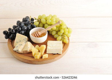 cheese plate - various types of cheese, grapes green and black, honey on a wooden Board