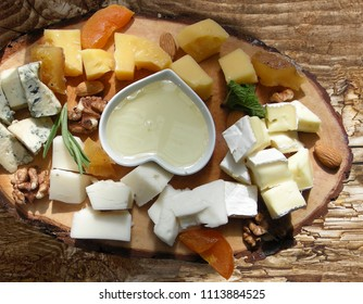 Cheese plate with various types of cheese, honey,almonds, dried apricots and nuts on a wooden board .
