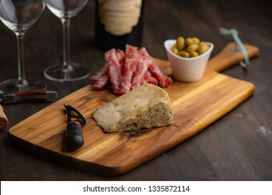 Cheese plate with wine in the background on a dark wood table