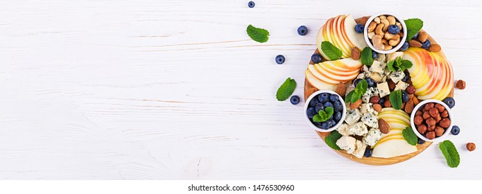 Cheese platter with assorted cheeses, blueberry, apples, nuts on white table. Italian cheese  platter and fruit. Banner. Top view, overhead