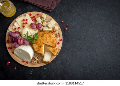 Cheese platter with assorted cheeses, grapes, nuts on black background, copy space. Italian cheese and fruit platter.