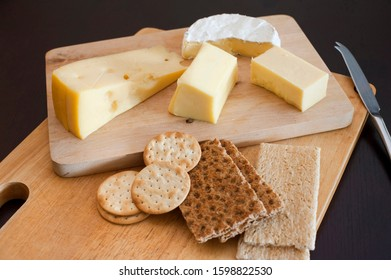 Cheese platter with an assortment of cheeses served with water biscuits and crackers on a dark background