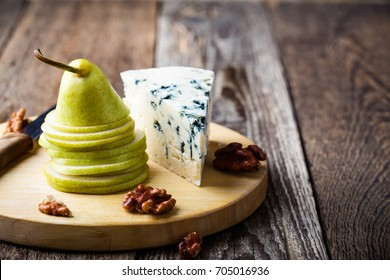Cheese platter. Blue cheese  with fresh pear on rustic wooden board