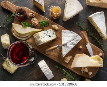 Cheese platter with different cheeses, fruits, nuts and wine on stone background. Top view. Tasty cheese starter.
