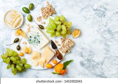 Cheese platter with different cheeses, grapes, nuts, honey. Appetizers table with antipasti snacks. Cheese variety board over white marble background. Top view, flat lay
