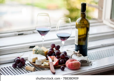 Cheese platter and glasses with wine on a window sill