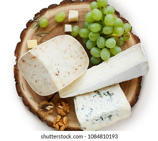 Cheese platter, gouda herb and blue roquefort cheese on wooden board with grapes and nuts isolated on white background, top view