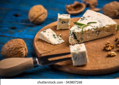 A cheese platter with nut on blue wooden table