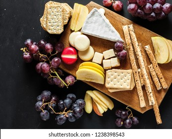 Cheese platter on cutting board with pieces of fresh apple and grains on a black chalkboard background