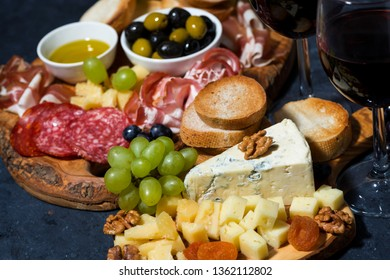 cheese platter on a wooden board, bread, fruit and cold cuts, closeup horizontal