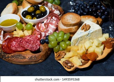 cheese platter on a wooden board, bread, fruit and cold cuts on dark background, closeup horizontal