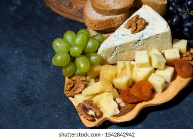 cheese platter on a wooden board, bread and fruit, top view horizontal