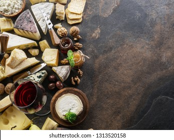 Cheese platter with organic cheeses, fruits, nuts and wine on stone background. Top view. Tasty cheese starter.
