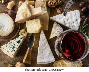 Cheese platter with organic cheeses, fruits, nuts and wine. Top view. Tasty cheese starter.