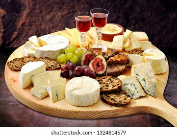 Cheese platter still-life with an impressive variety of European cheeses hard, soft and blue types. Raisin bread, fig and almond cake and a glaas of port to complement the taste of savoury cheeses.
