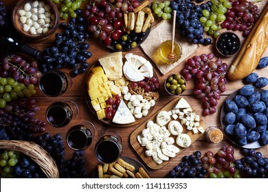 Cheese platter: variety of cheeses with fruits and bread served with grapes, honey, red wine, crackers, olives and nuts on a wooden background. Top view. Cheeseboard. Food flat lay.