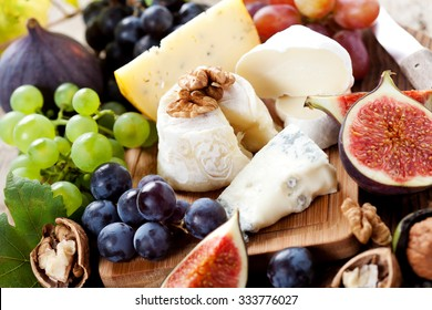 Cheese platter: variety of cheeses on wooden plate with fruits