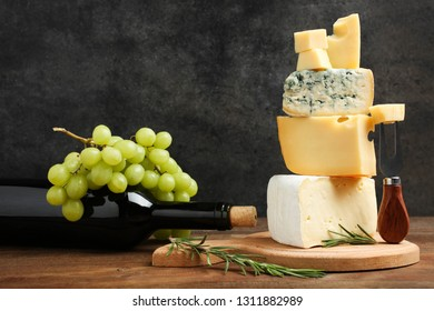 Cheese platter: yellow Maasdam, white Camembert and blue cheese Dor Blue with bottle of wine and grapes on wooden table on black background. Concept serving cheese.