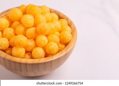 Cheese puff balls in wooden bowl on light background. Cinema snacks. Copy space