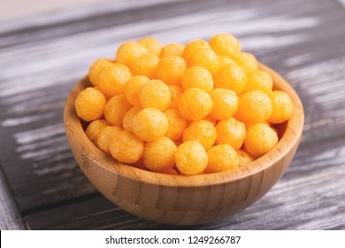 Cheese puff balls in wooden bowl on wooden background. Cinema snacks. Copy space