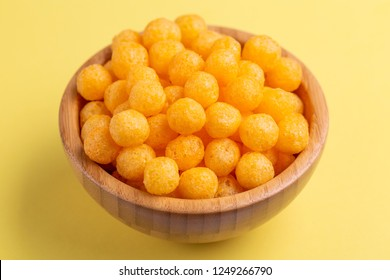 Cheese puff balls in wooden bowl on bright colorful background. Cinema snacks. Copy space