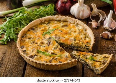 Cheese Quiche with chicken, arugula and mushrooms, homemade, wood desk