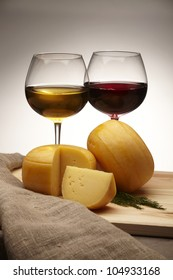 cheese with red and white wine on dark background