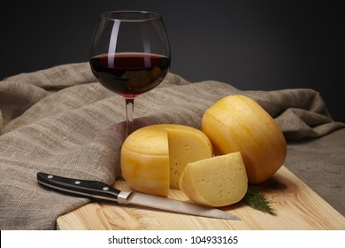 cheese with red wine on dark background