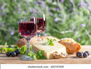 cheese with red wine on wooden table outdoors. sunny day