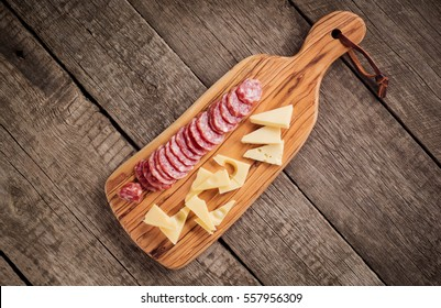 cheese and salami on kitchen board on rustic background. Top view with copy space .