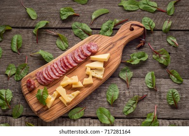 cheese and salami on kitchen board on rustic background. Top view with copy space and herbs .