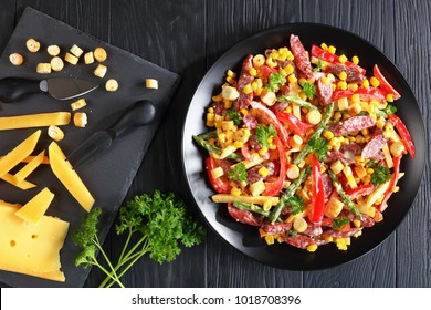 cheese, sausages, vegetables salad  served on black plate with ingredients on slate tray, view from above, close-up