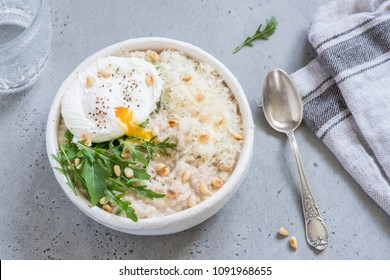 Cheese savoury oatmeal with poached egg, arugula and pine nut