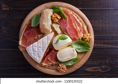 Cheese selection on wooden rustic background. Cheese platter with different cheeses, jamon or prosciutto. View from above, top studio shot