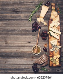 Cheese selection on wooden rustic board. Cheese platter with different cheeses, grapes, nuts, honey and dates on weathered wood background.