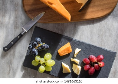 Cheese selection served with red white and black grapes. Flatlay snack food image. Leicester and cheddar hard cheeses with fruit served on wood and slate coasters with knife flat lay food photography.