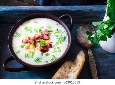 Cheese soup with bacon and corn in ceramic bowl.Dark blue scratched background. Selective focus.