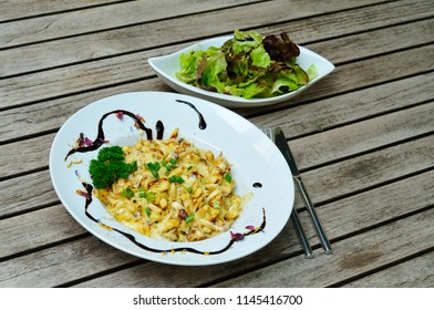 Cheese spaetzle on a plate with a salad.