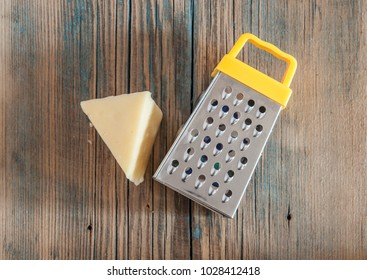 Cheese and steel grater on a wood kitchen table