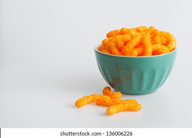 Cheese sticks in a green bowl on a white background