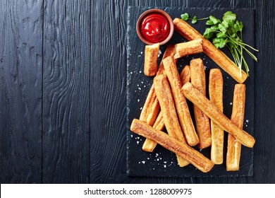 Cheese Straws, Cheesy Bread Sticks on a cutting wooden board with tomato sauce on a black wooden table, view from above, close-up, flatlay, copy space