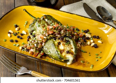 Cheese stuffed roasted Poblano pepper with fresh salsa sitting on yellow plate