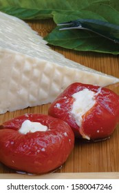 Cheese stuffed tomato appetizer, feta cheese slices and basil leaves. Delicious cheese presentations, Turkish appetizers, tomatoes, cheeses concepts. Vertical close-up shot.